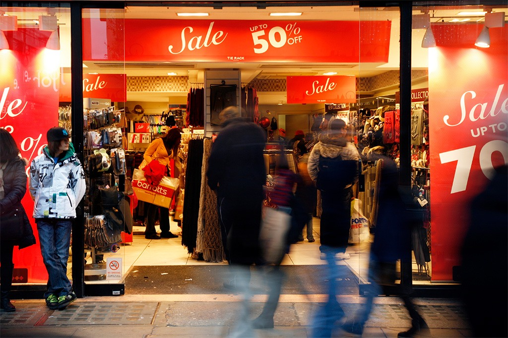 Shoppers in front of a Retail sale shop