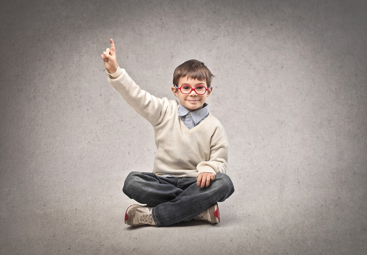 A child in glasses raises his hand