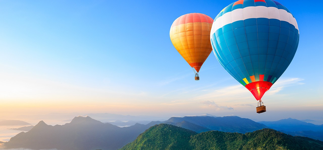 Hot Air Balloons Floating Over Mountains