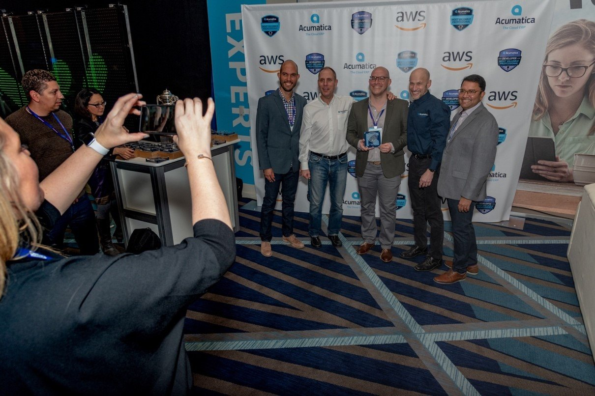 Acumatica's Jon Roskill, Ajoy Krishnamoorthy and Mark Franks posing with MVP winners during Sunday's welcome reception